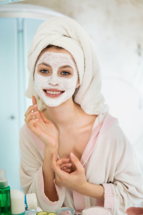 La mujer se ocupa la cara hace una máscara fotos de archivo libres de regalías