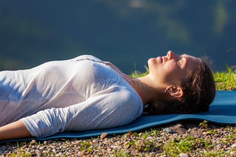 La mujer se relaja en el asana Savasana de la yoga al aire libre foto de archivo libre de regalías