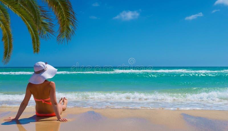 La mujer se relaja en la playa imagen de archivo