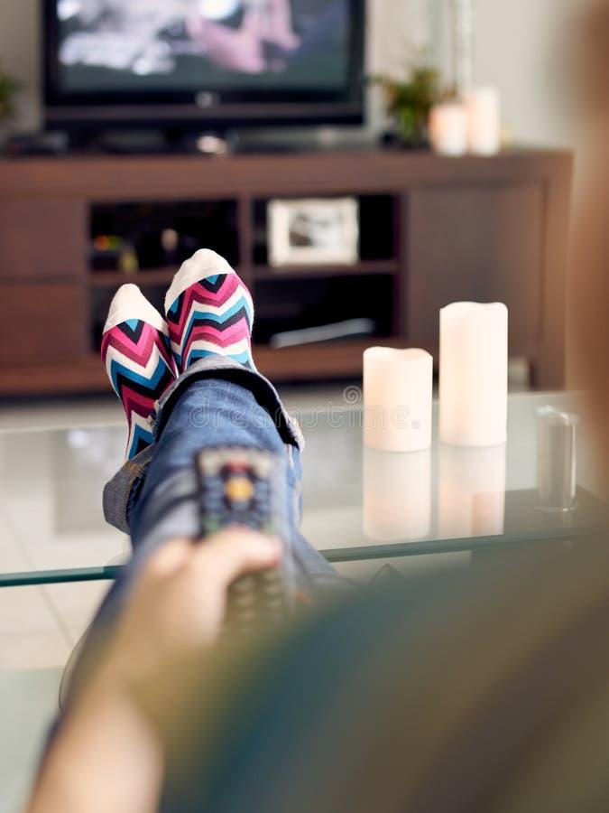 La mujer se relaja en Sofa Watching Film On TV con el telecontrol foto de archivo
