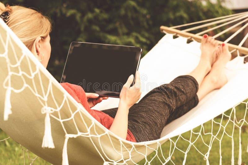 La mujer se relaja en una hamaca fotos de archivo libres de regalías