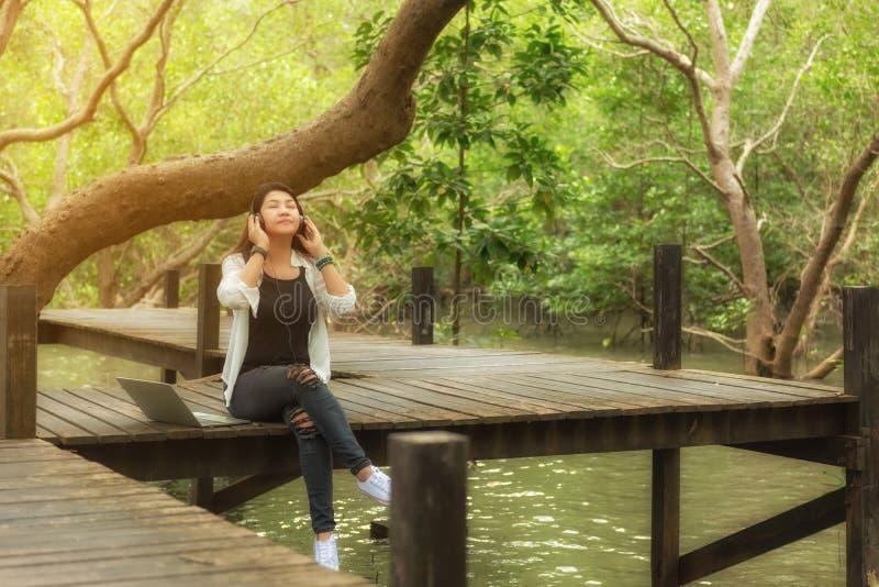 La mujer se relaja y leyendo un libro mientras que música que escucha con el auricular y el ordenador portátil en el parque del v fotos de archivo