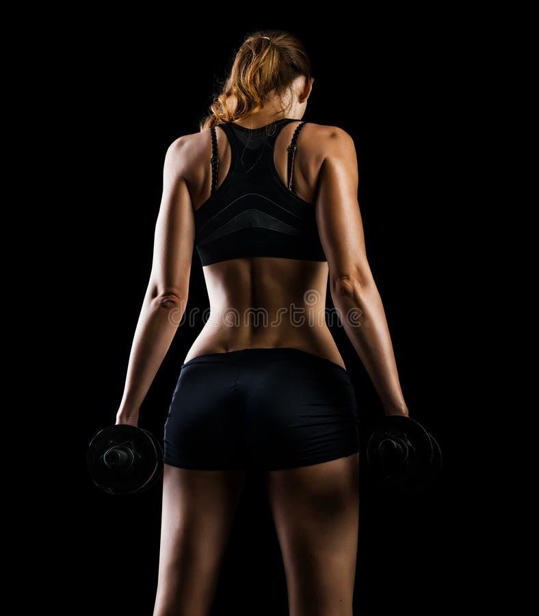 La mujer se resuelve con pesas de gimnasia en negro en estudio foto de archivo libre de regalías