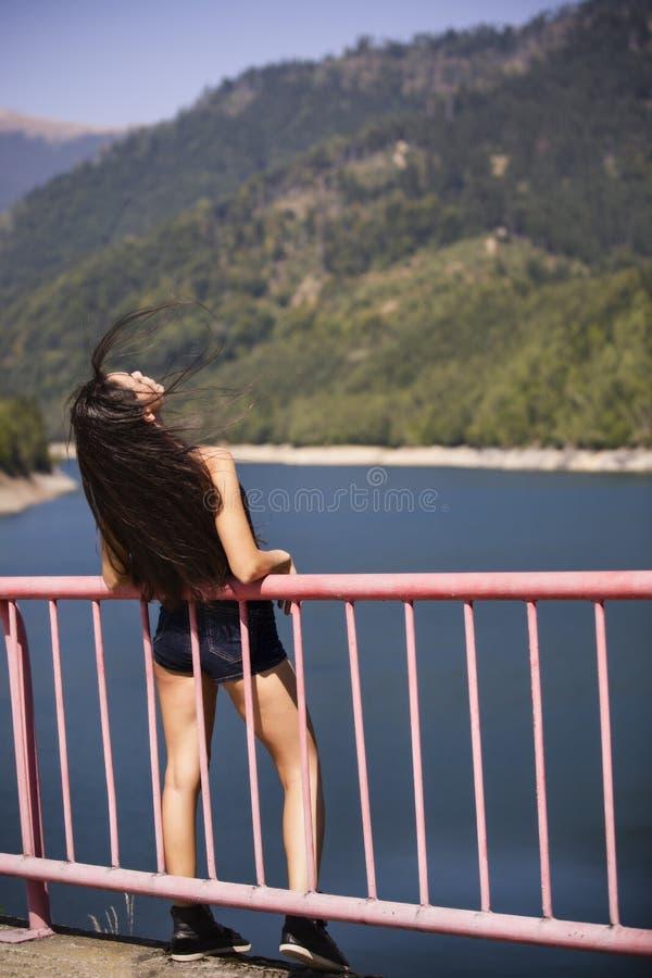 La mujer se sienta al borde de una presa foto de archivo