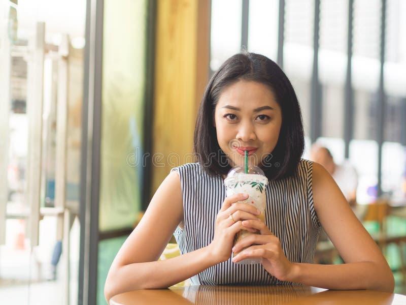 La mujer se sienta en café helado wirh del café del café en la tabla foto de archivo