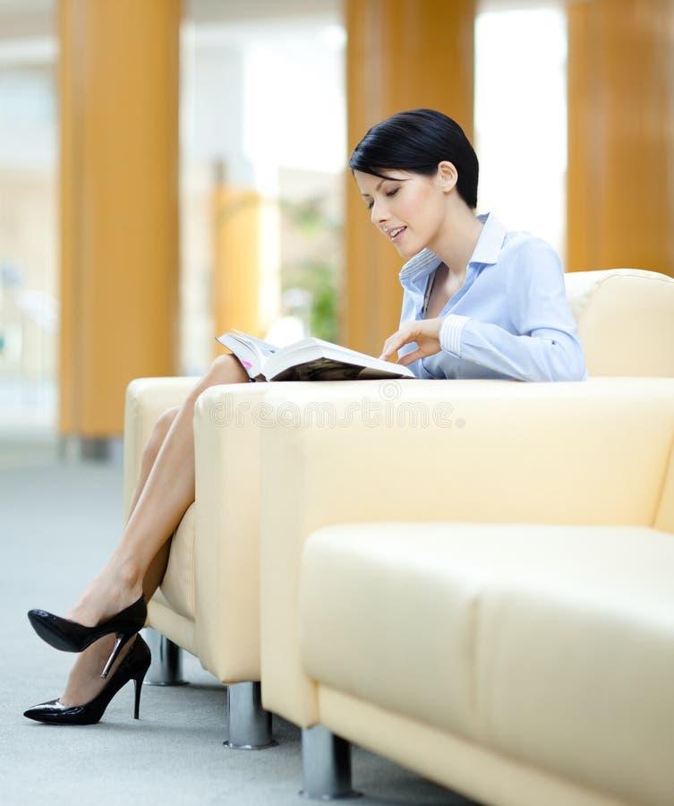 La mujer se sienta en el sofá con el libro imagen de archivo libre de regalías