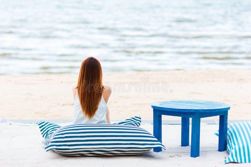 La mujer se sienta en la playa fotos de archivo libres de regalías