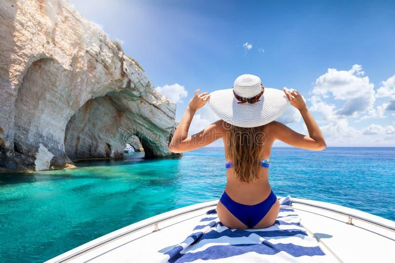 La mujer se sienta en un barco y goza de las cuevas azules de la isla de Zakynthos, mar jónico, Grecia foto de archivo