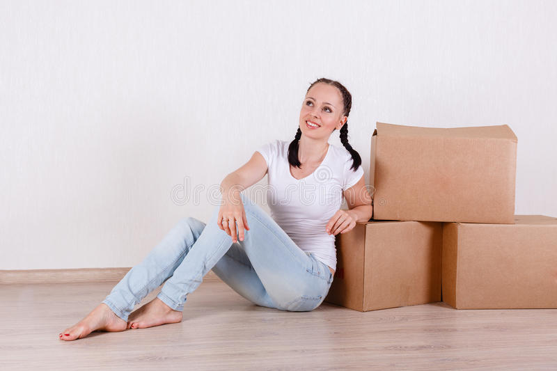 La mujer se sienta en un cuarto cerca de las cajas fotos de archivo