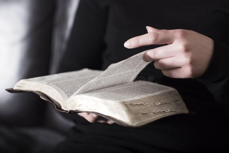 La mujer se sienta en un sofá y leyó la biblia imágenes de archivo libres de regalías