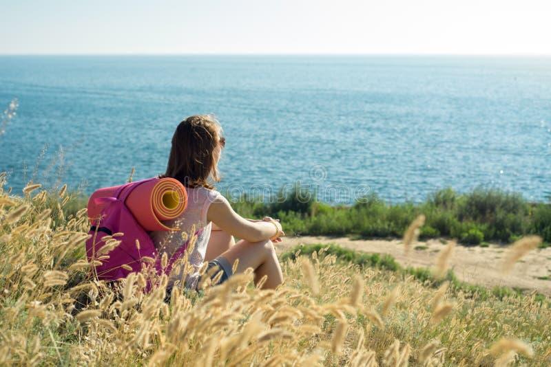 La mujer se sienta en una ladera y mira hacia fuera al mar fotografía de archivo libre de regalías
