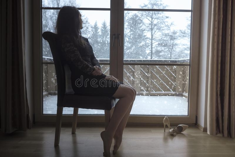 La mujer se sienta en una silla delante de las puertas de cristal foto de archivo