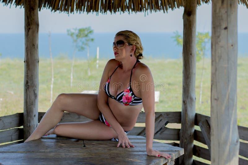 La mujer se sienta en una tabla contra la perspectiva del mar foto de archivo libre de regalías