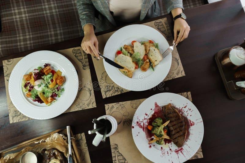 La mujer se sienta en una tabla de cena con la ensalada del ensalada César, vegetal con el huevo escalfado y el filete asado a la imagen de archivo libre de regalías