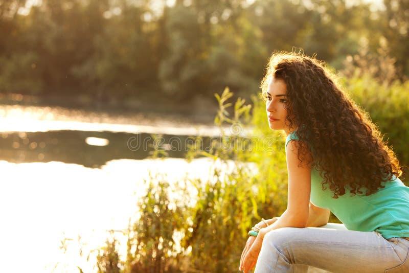 La mujer se sienta por el lago imagen de archivo