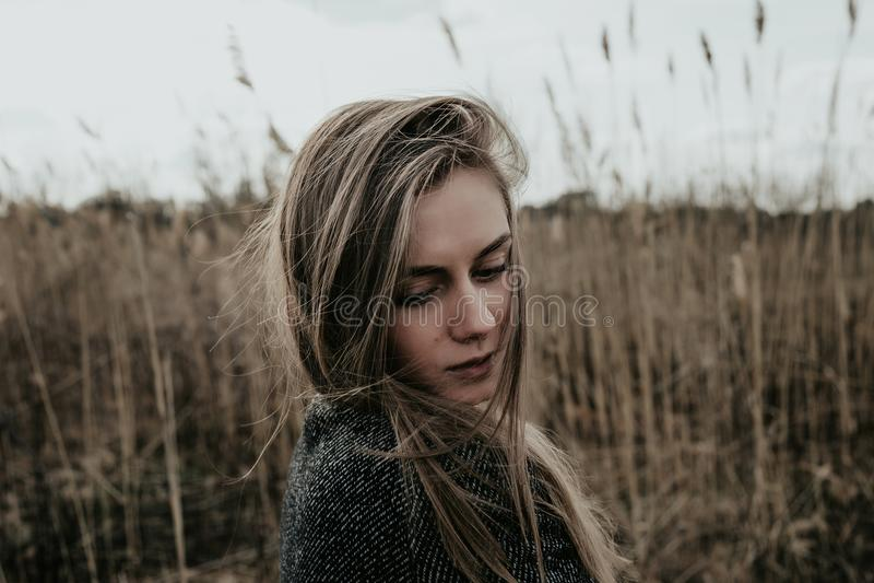 La mujer se vistió en la capa de las lanas que miraba abajo sobre su hombro Espadaña del fondo outdoor Tiro medio foto de archivo libre de regalías