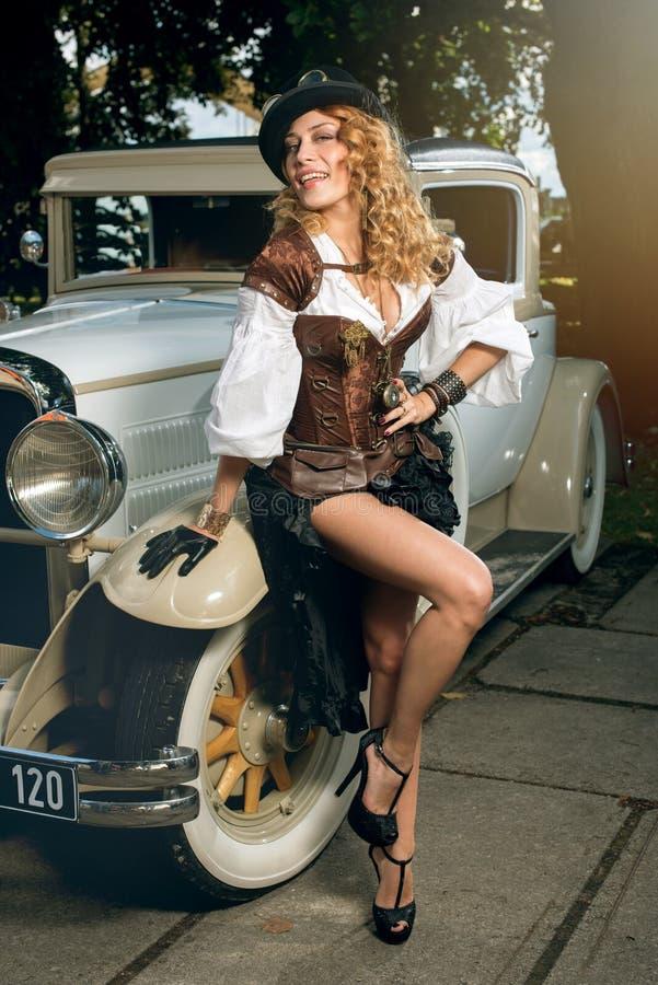 La mujer se vistió en el estilo del steampunk que presentaba sobre el coche retro foto de archivo