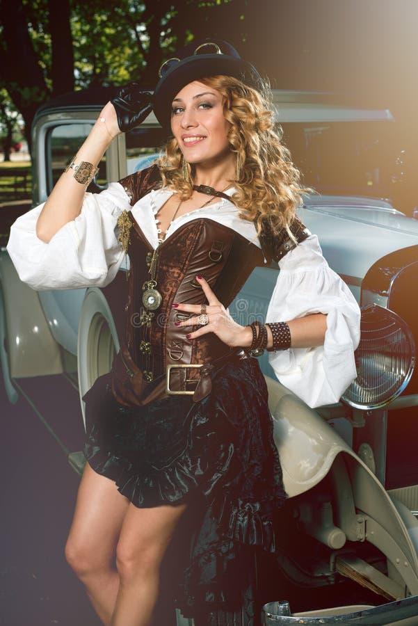 La mujer se vistió en el estilo del steampunk que presentaba sobre el coche retro imagenes de archivo