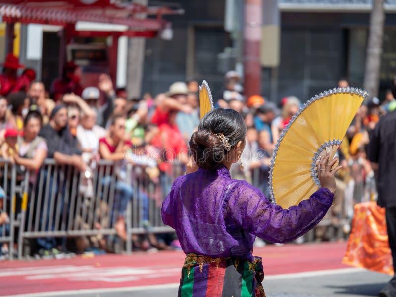 La mujer se vistió en fans mexicanas tradicionales de las ondas del desgaste delante de fotografía de archivo libre de regalías