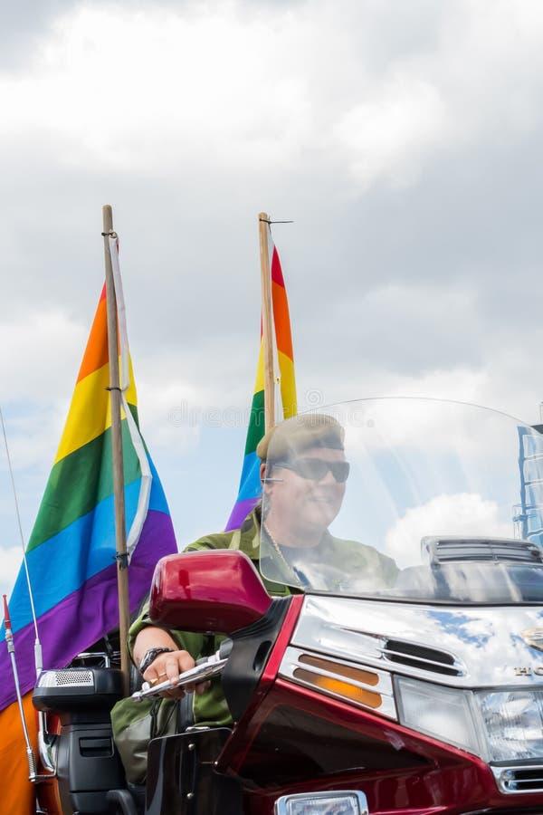 La mujer se vistió en moto militar del montar a caballo del estilo con el arco iris durante Estocolmo Pride Parade fotografía de archivo