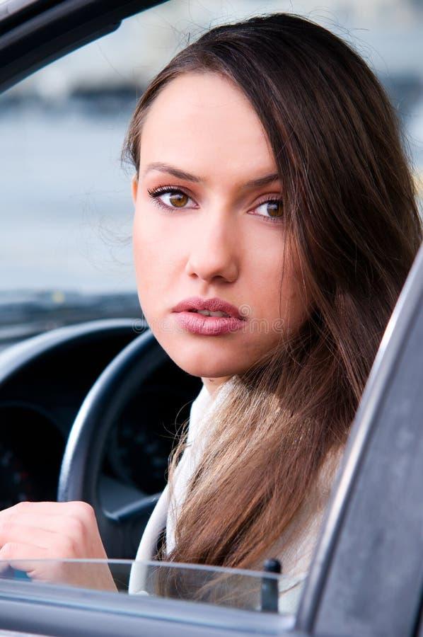 La mujer sensual está mirando la cámara de un coche fotografía de archivo libre de regalías