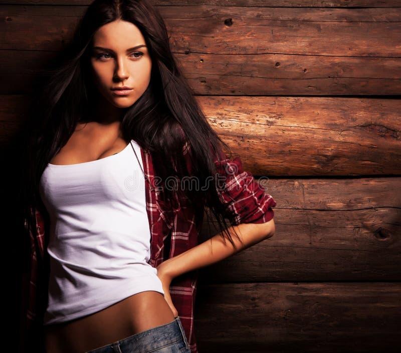 La mujer sensual y de la belleza joven en ropa casual presenta en fondo de madera del grunge imagenes de archivo