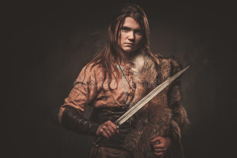 La mujer seria de vikingo con la espada en un guerrero tradicional viste, presentando en un fondo oscuro foto de archivo