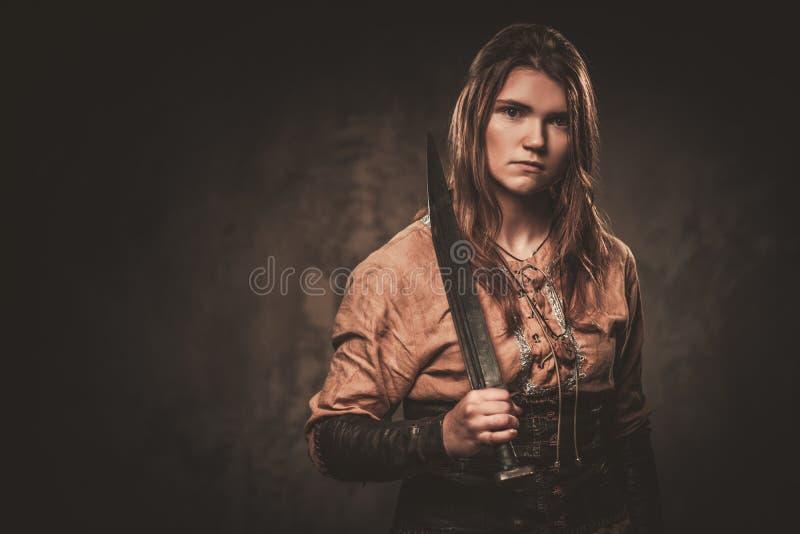 La mujer seria de vikingo con la espada en un guerrero tradicional viste, presentando en un fondo oscuro imagenes de archivo
