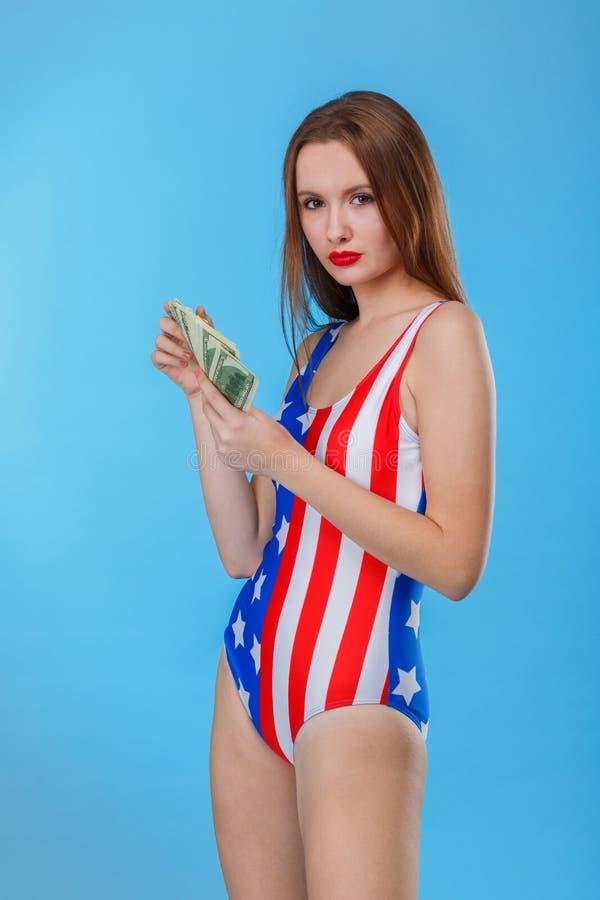 La mujer seria se vistió en monos con una impresión de la bandera americana que llevaba a cabo un manojo de billetes de dólar Fon foto de archivo