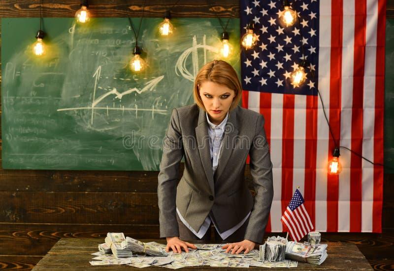 La mujer seria se vistió en trajes con una bandera americana que llevaba a cabo un manojo de dólar foto de archivo libre de regalías