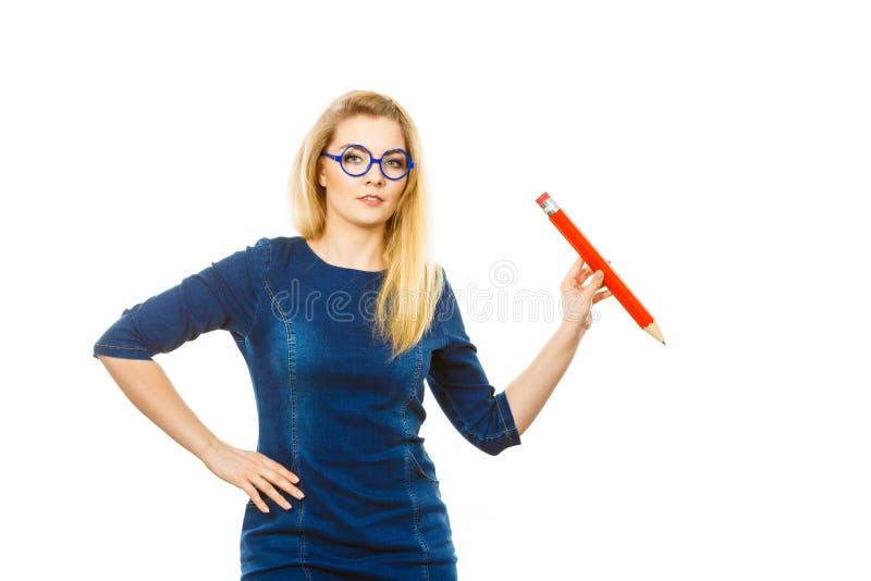 La mujer seria sostiene el l?piz grande disponible fotografía de archivo