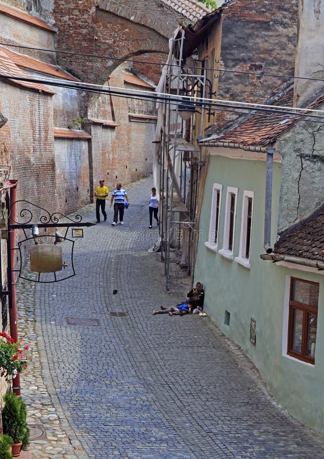 La mujer sin hogar, sucia y su hijo liying en el asfalto de la calle en Sibiu, Rumania imagenes de archivo