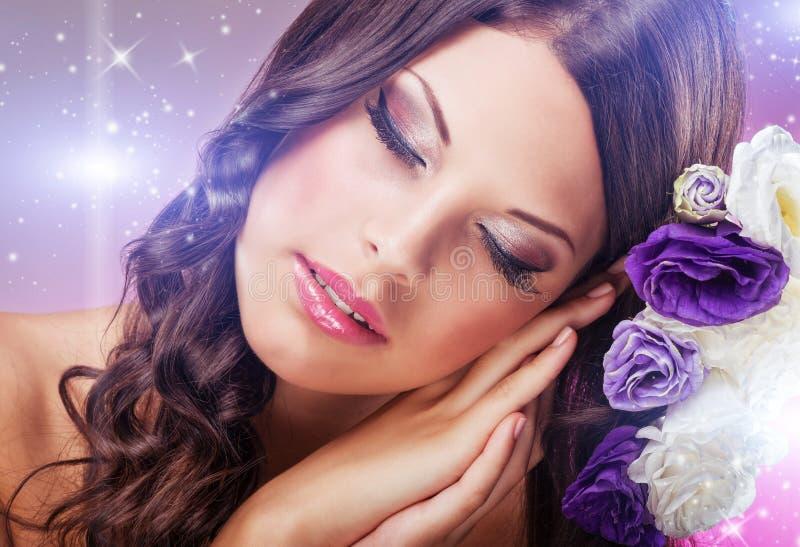 La mujer soñadora hermosa con los ojos se cerró, al lado de las flores púrpuras fotografía de archivo libre de regalías