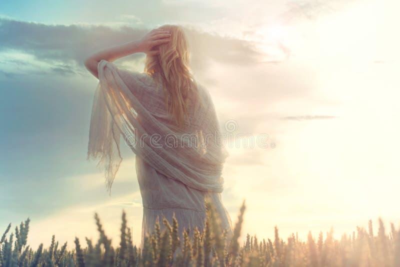 La mujer soñadora mira infinito mientras que sube el sol foto de archivo