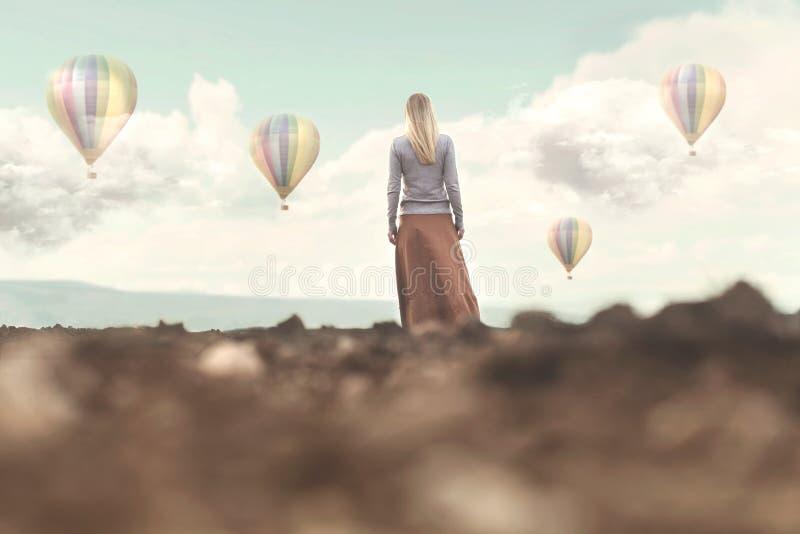La mujer soñadora que mira el aire caliente hincha bajar fotos de archivo libres de regalías