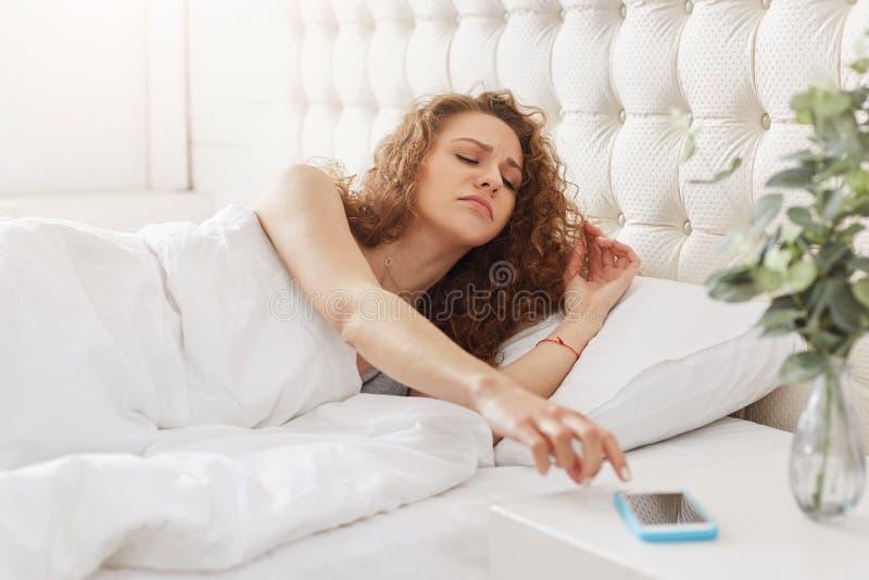 La mujer soñolienta con el pelo rizado apaga la alarma en el teléfono elegante, wak fotografía de archivo