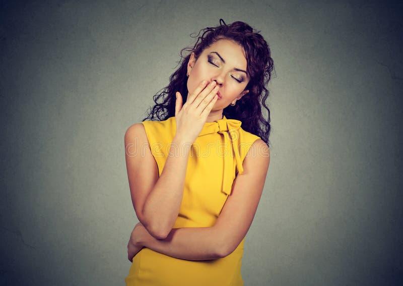 La mujer soñolienta con los ojos de bostezo de la boca abierta de par en par cerró parecer aburrida foto de archivo libre de regalías