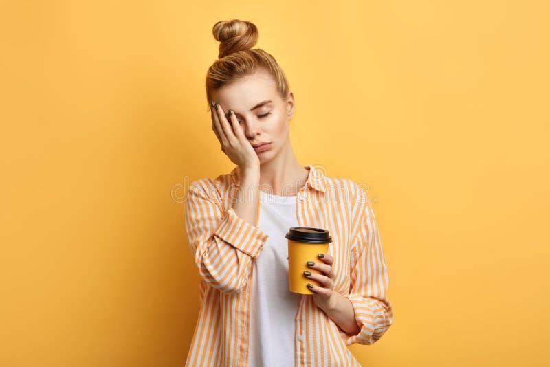 La mujer soñolienta de pelo rubio cansada sostiene una taza de café foto de archivo
