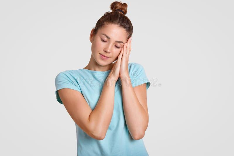 La mujer soñolienta se inclina en ambas palmas, mantiene ojos cerrados, vestido ropa casual, quiere tener resto después de noche  foto de archivo