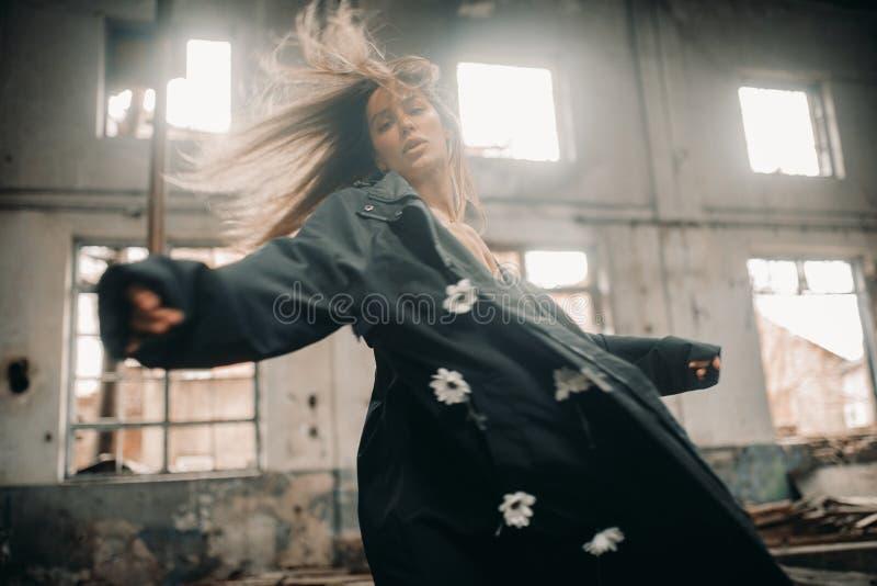 La mujer sola joven se coloca en el edificio abandonado imagen de archivo