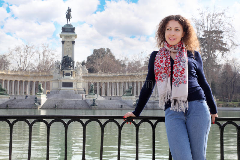 La mujer sonríe y se inclina en la verja en el fondo del monumento imagenes de archivo