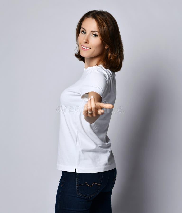 La mujer sonriente agradable en la camiseta y los tejanos blancos lleva a cabo hacia fuera su mano y llamadas para seguirla en al imagen de archivo libre de regalías