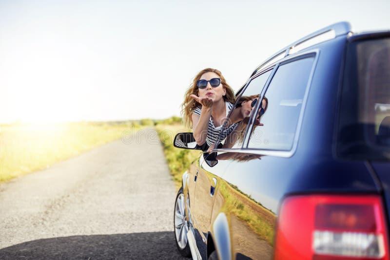 La mujer sonriente atractiva envía un beso del aire de la ventanilla del coche en un día de verano fotos de archivo