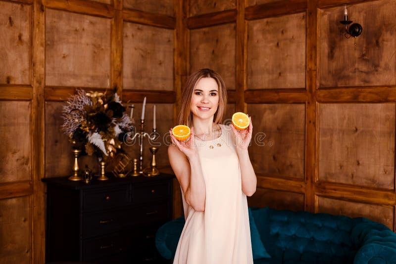 La mujer sonriente atractiva joven muestra dos naranjas anaranjadas enteras imagenes de archivo