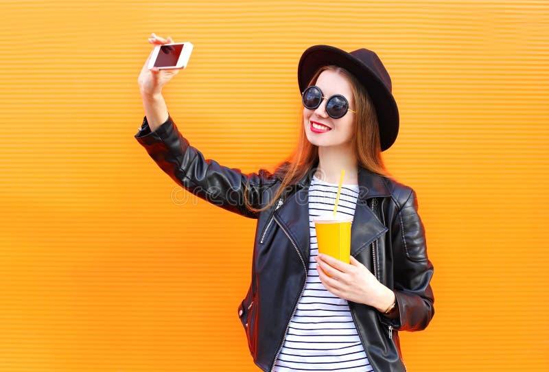 La mujer sonriente bonita de la moda hace el autorretrato en smartphone en estilo negro de la roca sobre naranja de la ciudad imagenes de archivo