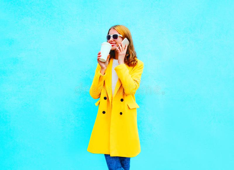 La mujer sonriente bonita de la moda habla en un smartphone con la taza de café fotos de archivo