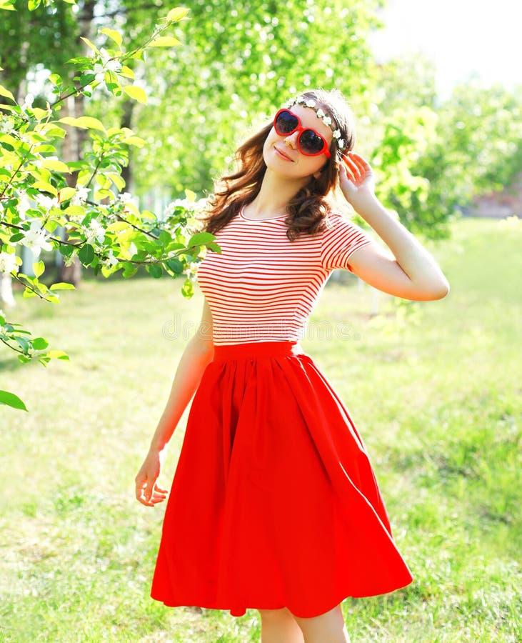 La mujer sonriente bonita en falda roja y el corazón forman las gafas de sol fotos de archivo libres de regalías