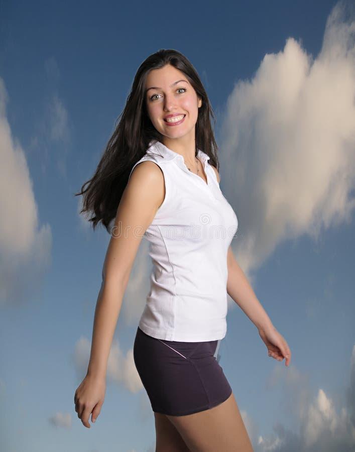 la mujer sonriente camina enérgicamente las nubes y cielo azul detrás de ella imágenes de archivo libres de regalías