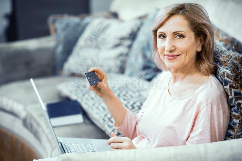 La mujer sonriente celebra un funcionamiento del ordenador portátil del hogar fotos de archivo libres de regalías