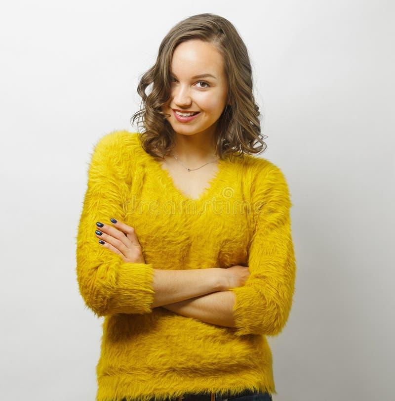 La mujer sonriente con sonrisa atractiva en ropa brillante del color se coloca sobre fondo aislado blanco fotos de archivo